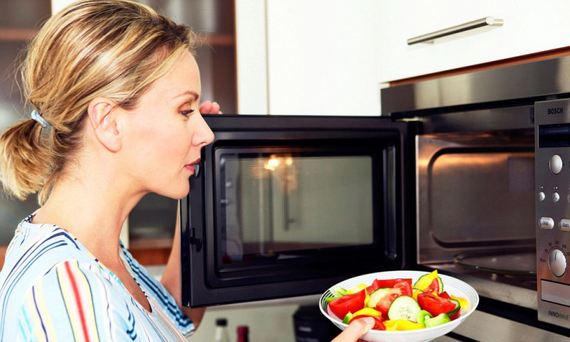 Frau erwaermt Essen in der Mikrowelle, woman in kitchen use microwave